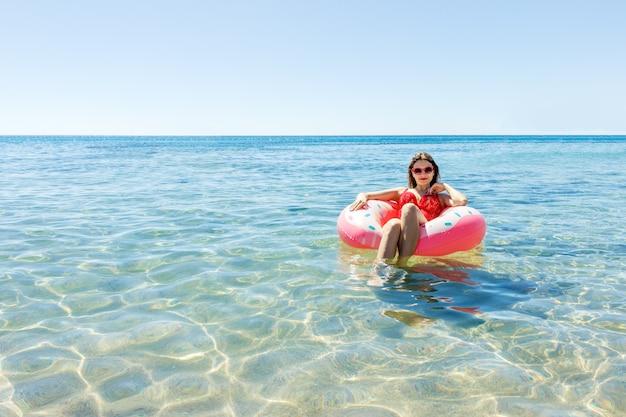 Schöne junge frau mit aufblasbarem donut im meer