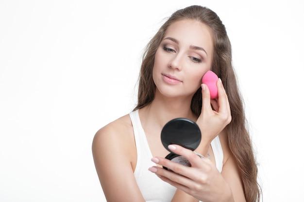 Schöne junge frau mit beauty-mixer zum auftragen von foundation für make-up auf gesicht isoliert auf weißem hintergrund