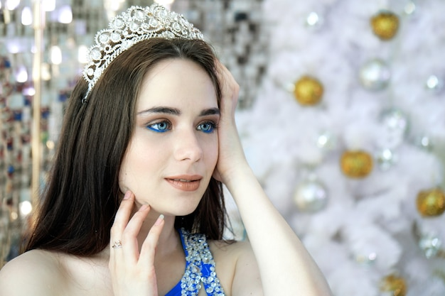 Schöne junge frau mit blauen augen, die eine krone und ein festliches blaues kleid tragen, das auf dem neujahrsdekorationshintergrund aufwirft. weihnachtsprinzessin vor weiß geschmücktem weihnachtsbaum.