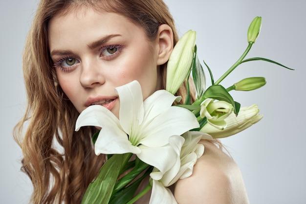 Schöne junge frau mit blume, die im studio auf einem hellen hintergrund, romantisches zartes bild, frauenporträt aufwirft