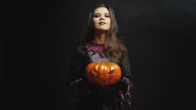 Schöne junge frau mit bösem gesicht, gekleidet wie eine hexe, die einen kürbis für halloween über einem schwarzen hintergrund hält