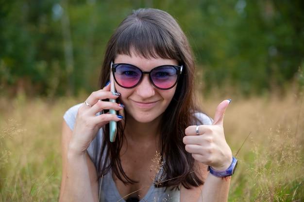 Schöne junge frau mit brille, die am telefon lächelt und den daumen mit einem glücklichen lächeln zeigt