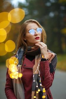 Schöne junge frau mit brille, die mit girlanden im herbstpark spielt