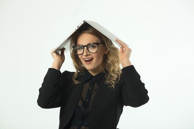 Schöne junge frau mit brille in einem schwarzen anzug mit einem laptop an einer weißen wand