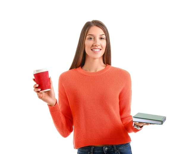 Schöne junge frau mit buch und kaffee auf weiß
