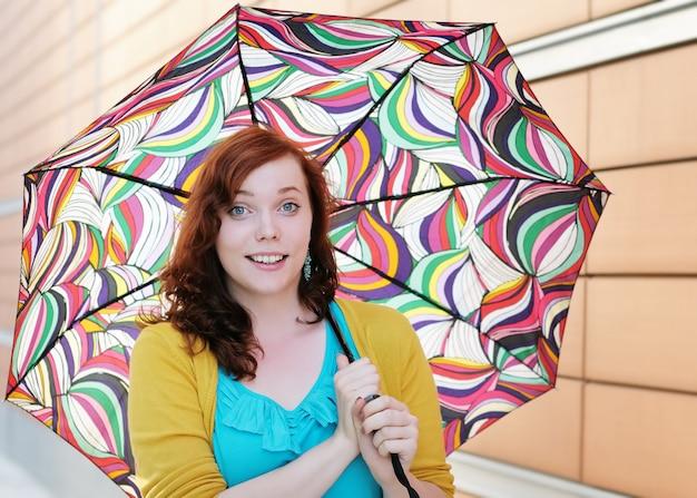 Schöne junge frau mit buntem regenschirm