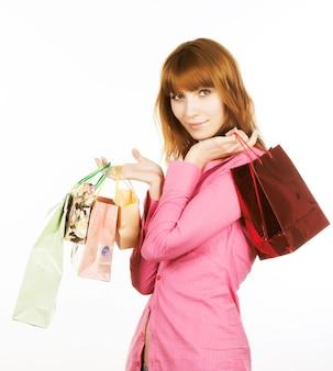 Schöne junge frau mit bunten einkaufstüten in ihrer hand