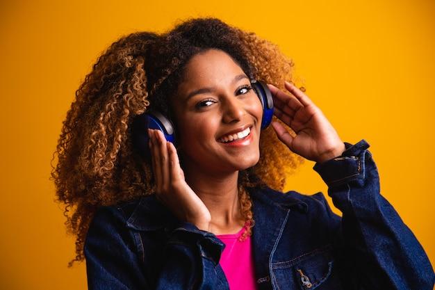Schöne junge frau mit dem afrohaar, das musik mit dem kopfhörerlächeln hört.