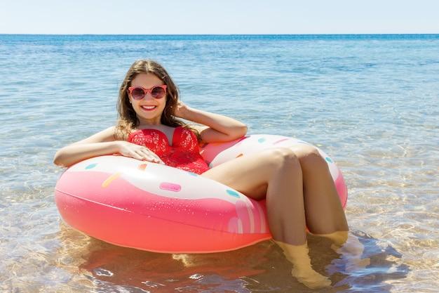Schöne junge frau mit dem aufblasbaren ring, der im blauen meer sich entspannt