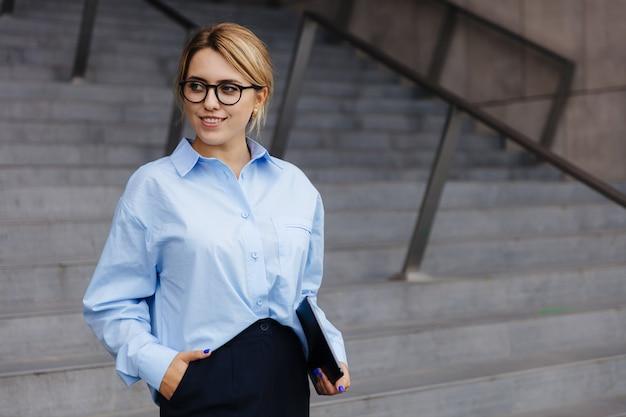 Schöne junge frau mit dem blonden haar, die auf treppen steht und digitale tablette hält. lächelnde frau mit brille, blauem hemd und schwarzer hose.