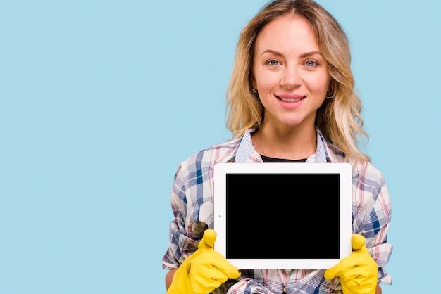 Schöne junge frau mit dem gelben handschuh, der die digitale tablette steht gegen blauen hintergrund hält