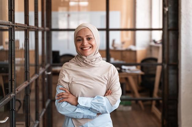 Schöne junge frau mit dem hijab, die im büro arbeitet
