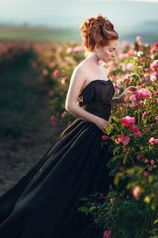 Schöne junge frau mit dem langen lockigen haar, das nahe rosen in einem garten aufwirft