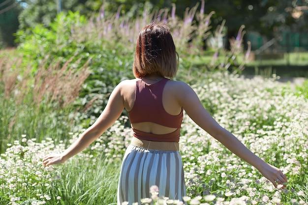 Schöne junge frau mit dem langen lockigen haar gekleidet im boho-artkleid, das in einem feld mit löwenzahn aufwirft.