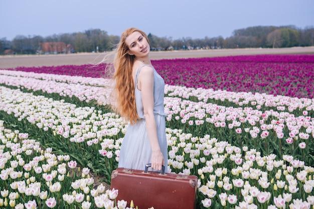 Schöne junge frau mit dem langen roten haar, das im weißen kleid steht mit altem weinlesekoffer auf buntem tulpenfeld trägt.
