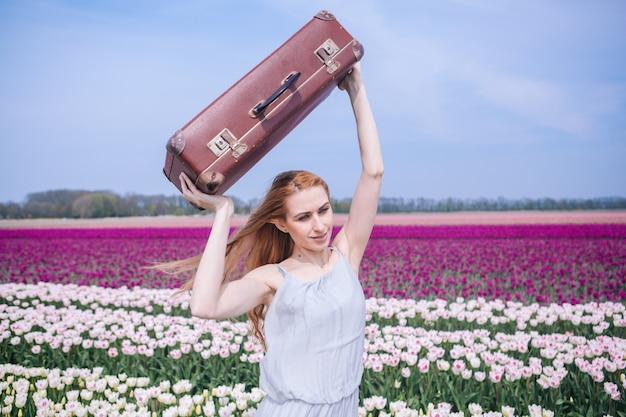 Schöne junge frau mit dem langen roten haar, das im weißen kleid steht mit gepäck auf buntem tulpenfeld trägt.