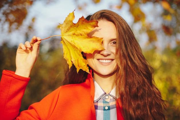 Schöne junge frau mit dem langen welligen haar, das gesicht mit einem blatt bedeckt