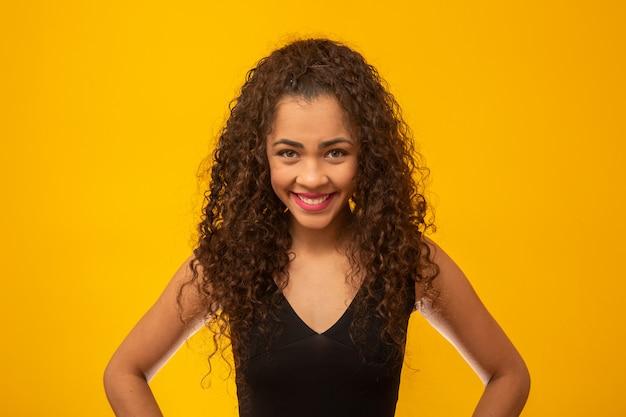 Schöne junge frau mit dem lockigen haar auf gelb