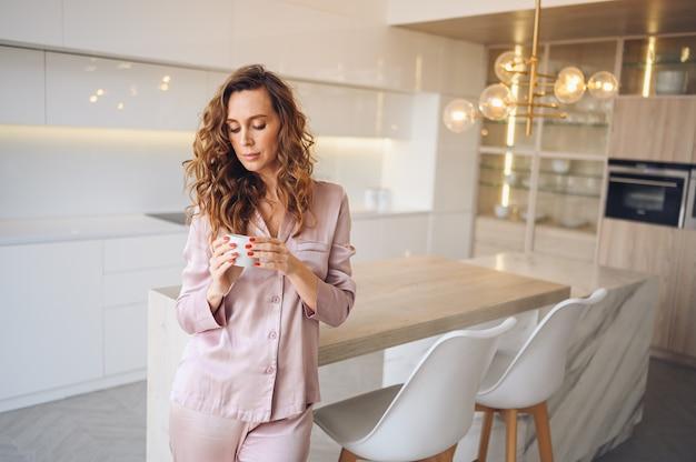 Schöne junge frau mit dem lockigen haar, das kaffee am wochenendmorgen im kuscheligen rosa pyjama trinkt. dame im modernen interieur der weißen küche des skandinavischen stils.