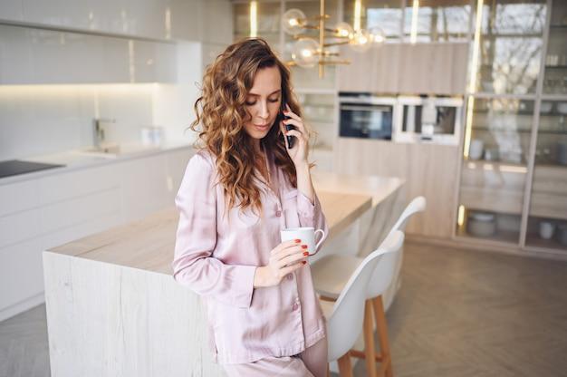 Schöne junge frau mit dem lockigen haar, das kaffee zu hause am faulen wochenendmorgen im gemütlichen rosa pyjama trinkt.