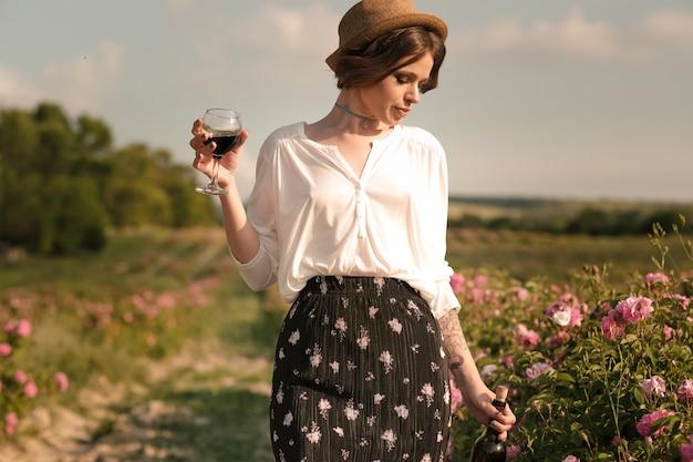 Schöne junge frau mit dem lockigen haar, das nahe rosen in einem garten aufwirft. das konzept der parfümwerbung.