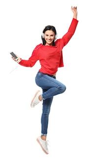 Schöne junge frau mit dem mobiltelefon, das musik auf weißem hintergrund hört