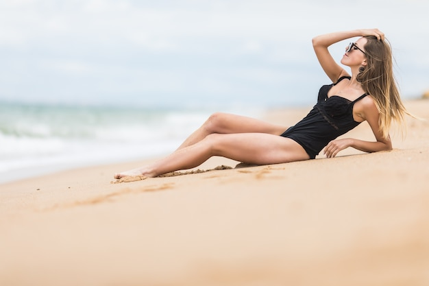 Schöne junge frau mit dem perfekten körper, der unten am strand liegt