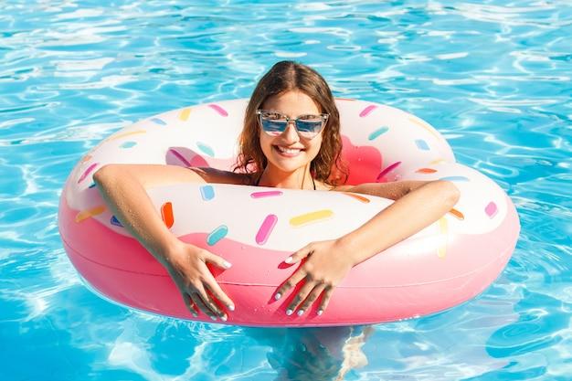 Schöne junge frau mit dem rosa kreis, der im blauen swimmingpool sich entspannt