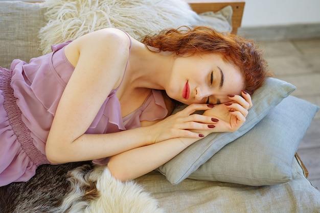 Schöne junge frau mit dem roten haar, das auf der couch liegt.