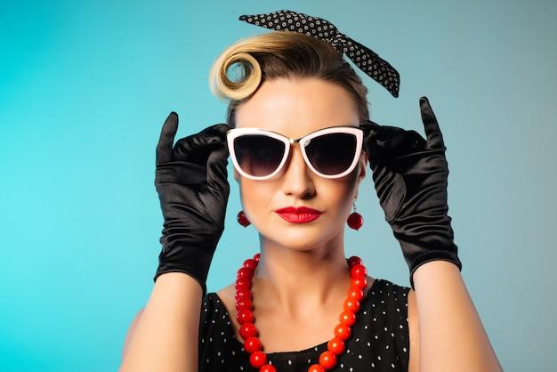 Schöne junge frau mit den glamourösen roten lippen, die sonnenbrillen-pinup-art tragen