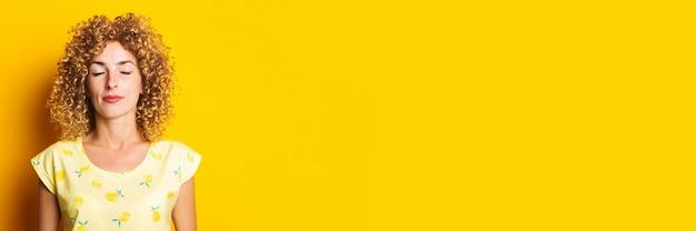 Schöne junge frau mit den lockigen haaren mit geschlossenen augen auf gelbem grund