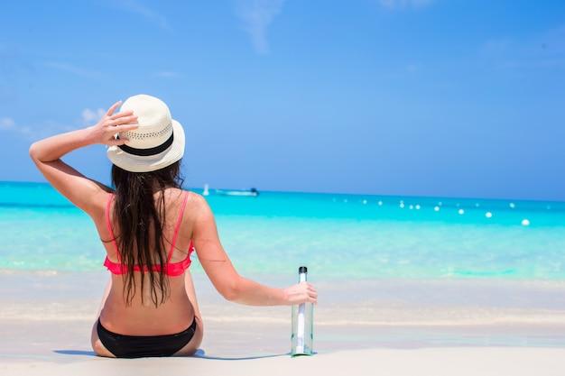 Schöne junge frau mit der flasche, die auf dem strand sitzt