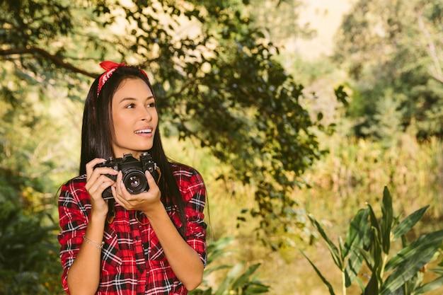 Schöne junge frau mit der kamera, die weg schaut