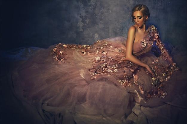 Schöne junge frau mit der luxuriösen aufstellung des blonden haares