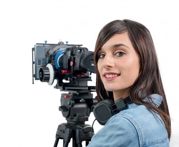 Schöne junge frau mit dslr-videokamera und kopfhörern