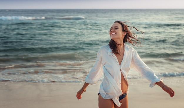 Schöne junge frau mit dunklem haar in einem weißen hemd auf dem ozean