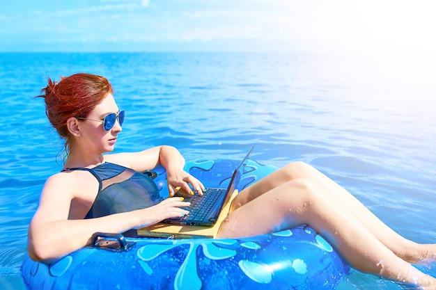 Schöne junge frau mit einem aufblasbaren ring und einem laptop, die im meer sich entspannen. workaholic-konzept