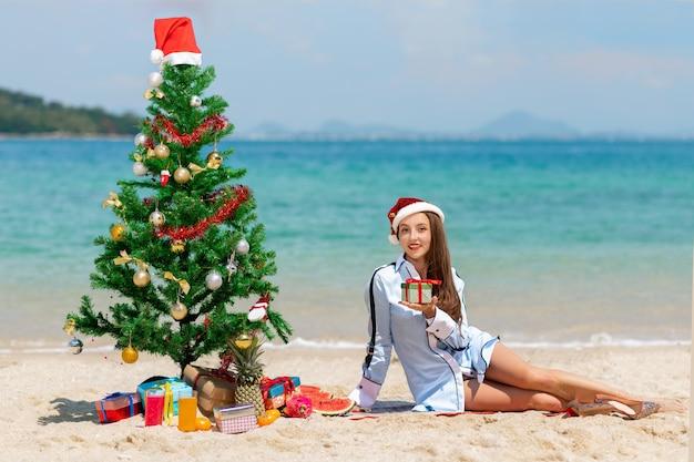 Schöne junge frau mit einem geschenk in ihrer hand feiert weihnachten und neujahr am strand in einer weihnachtsmütze.