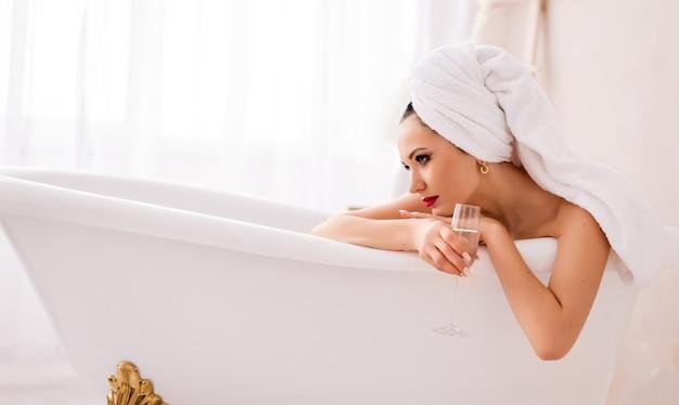 Schöne junge frau mit einem glas champagner im badezimmer. ein mädchen mit einem weißen handtuch auf dem kopf ruht im badezimmer. das konzept von luxus und glamour.
