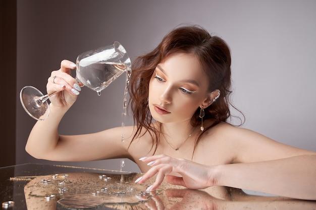 Schöne junge frau mit einem glas und schmuck in ihren händen. professionelles make-up, ausdrucksstarke augen