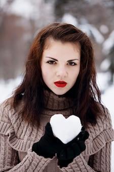 Schöne junge frau mit einem herzen aus schnee in ihren händen