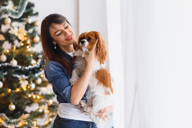 Schöne junge frau mit einem hund nahe weihnachtsbaum