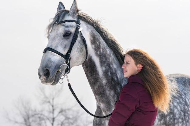 Schöne junge frau mit einem pferd auf der natur im winter auf schnee