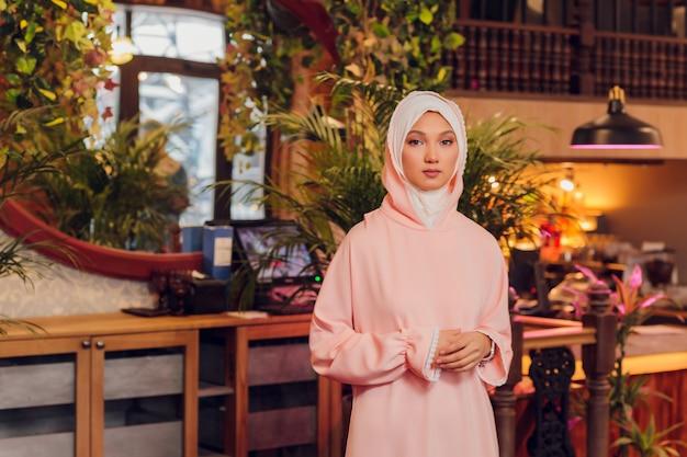 Schöne junge frau mit einem rosa hijab.