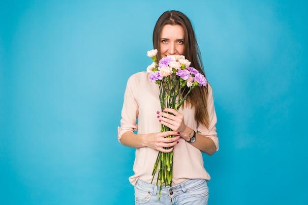Schöne junge frau mit einem strauß nelken auf blauem hintergrund, feminin, feier.