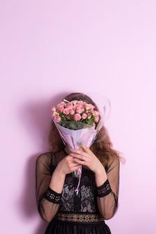 Schöne junge frau mit einem strauß zarter rosiger rosen