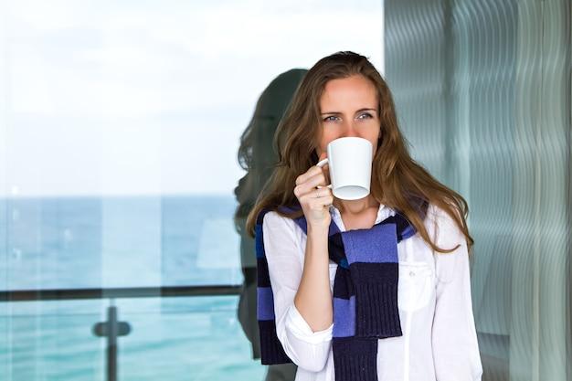 Schöne junge frau mit einer tasse in der hand, die am panoramafenster auf dem balkon steht