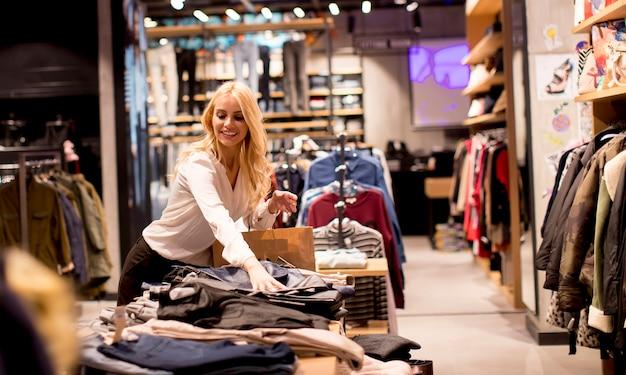 Schöne junge frau mit einkaufstaschen, die am bekleidungsgeschäft stehen