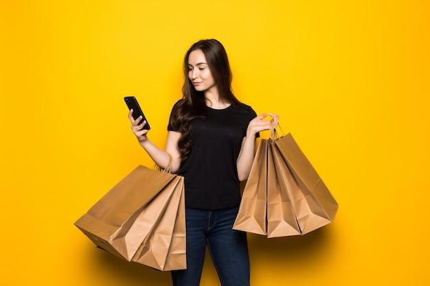Schöne junge frau mit einkaufstaschen unter verwendung ihres smartphones auf gelber wand. shopaholic shopping mode.