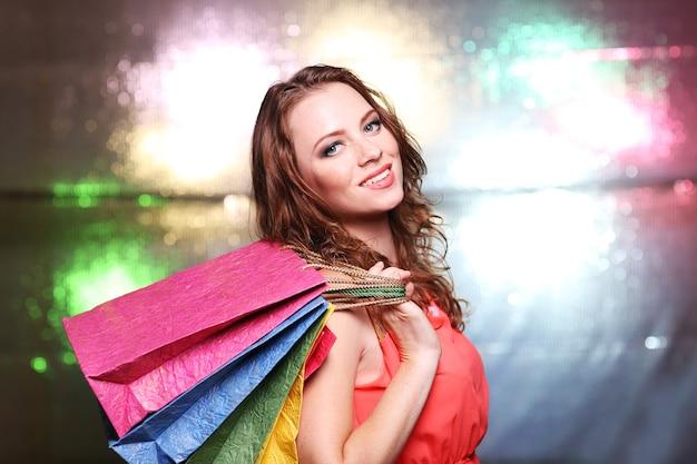 Schöne junge frau mit einkaufstüten auf heller oberfläche
